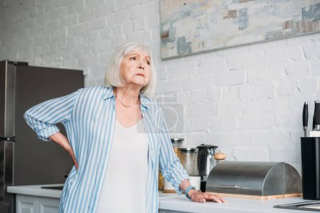 senior woman with back ache leaning on counter in kitchen