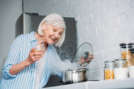 side view of smiling senior lady with glass of wine checking saucepan on stove in kitchen