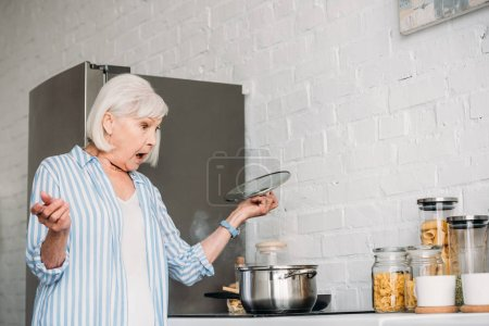 side view of shocked senior lady checking saucepan on stove in kitchen