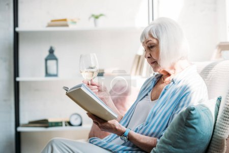 side view of focused senior woman with glass of wine reading book on couch at home