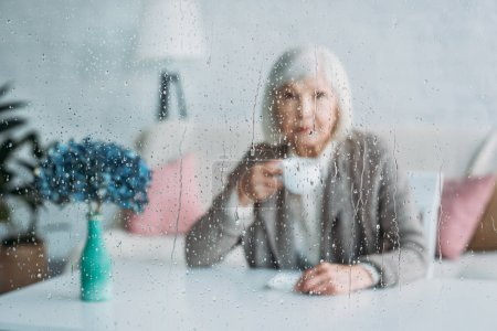 selective focus of senior woman with cup of coffee sitting at table at home