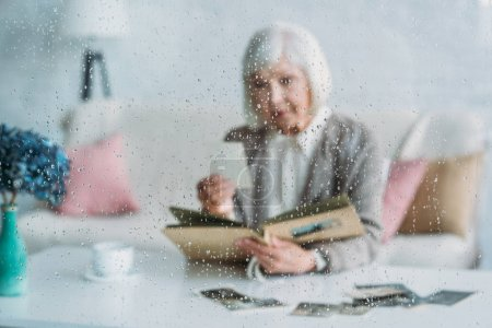 selective focus of senior woman looking at photographs in photo album at table with cup of coffee at home