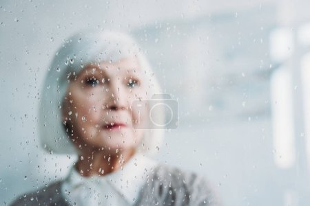 selective focus of thoughtful senior woman in knitted jacket looking away at home