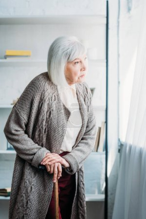 side view of pensive senior lady with walking stick standing in room at home