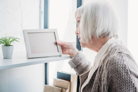 side view of senior lady looking at empty photo frame on bookshelf at home