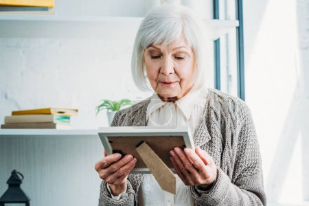 portrait of thoughtful senior lady in knitted jacket looking at photo frame in hands at home