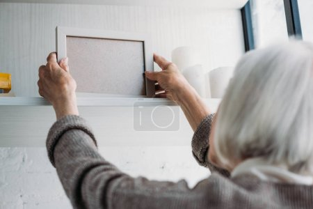 partial view of senior lady taking empty photo frame from bookshelf at home