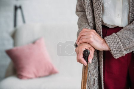 cropped shot of senior lady with wooden walking stick at home