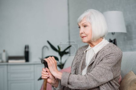 side view of grey hair lady with wooden walking stick resting on couch at home
