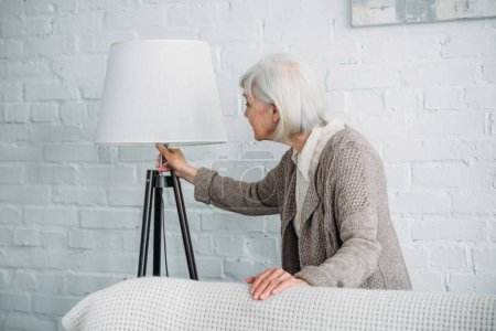 grey hair lady turning on standing lamp at home