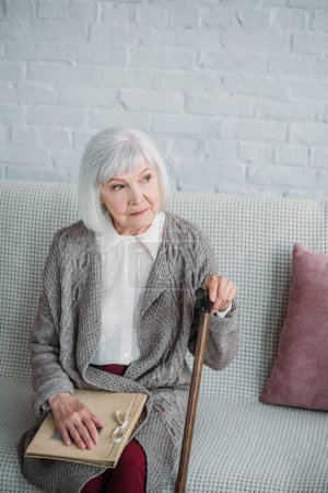 thoughtful senior lady with photo album resting on couch at home
