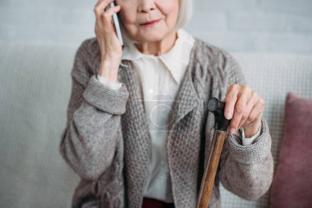 partial view of senior woman with walking stick talking on smartphone at home