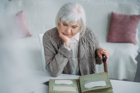 portrait of grey hair woman looking at photos in photo album at table at home