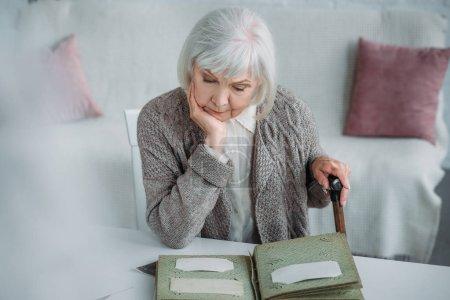 Photo pour Portrait de femme cheveux gris, regarder des photos dans l'album photo à table à la maison - image libre de droit