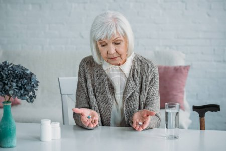 portrait of grey hair woman with pills in hands sitting at table alone at home