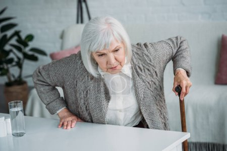 portrait of grey hair woman with walking stick trying to get up at home