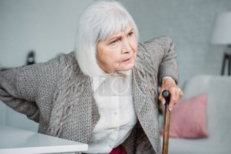 portrait of grey hair lady with back ache and wooden walking stick sitting on chair at home