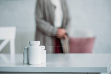 selective focus of senior woman with walking stick standing in room with medicines on tabletop at home