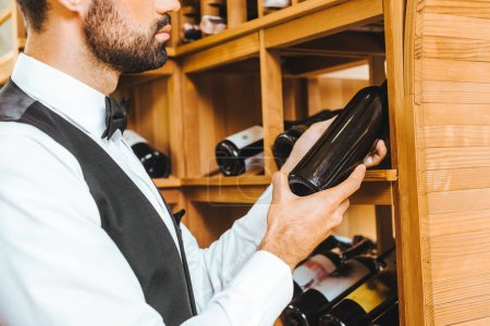 cropped shot of young wine steward taking bottle from shelf at wine store