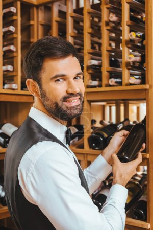 handsome young sommelier taking bottle from shelf at wine store and looking at camera