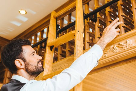 handsome young wine steward with ladder reaching for bottle on shelf at wine store