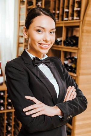 Photo for Smiling female wine steward with crossed arms looking at camera at wine store - Royalty Free Image