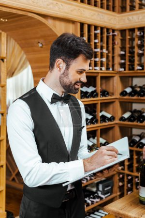 handsome young wine steward making notes at wine store