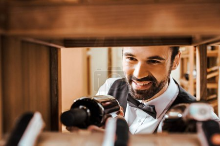 close-up shot of smiling young sommelier putting bottle on shelf at wine store