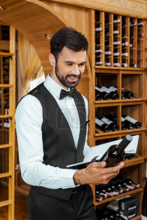 smiling young sommelier looking at bottle of wine and holding notebook at wine store