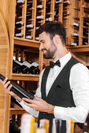 smiling young sommelier looking at bottle of wine at wine store