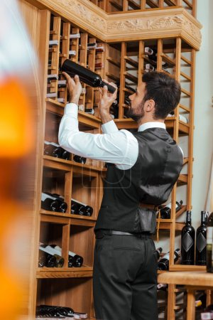 handsome young sommelier putting bottle on shelf at wine store