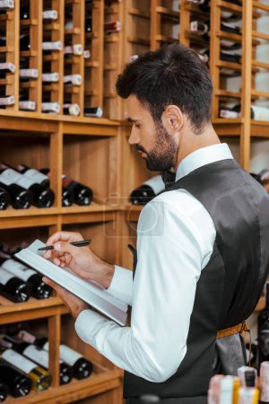 handsome young wine steward making notes near shelves at wine store