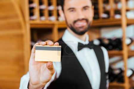 selective focus shot of young wine steward holding golden card at wine store