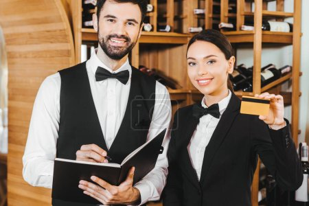 couple of wine stewards with notebook and golden credit card looking at camera at wine store