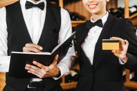 cropped shot of couple of wine stewards with notebook and golden credit card at wine store