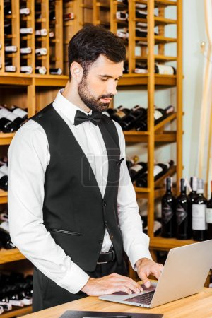 handsome young wine steward working with laptop at wine store