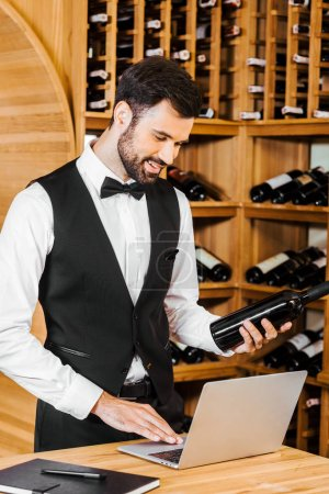 smiling young sommelier with bottle of wine making notes at wine store