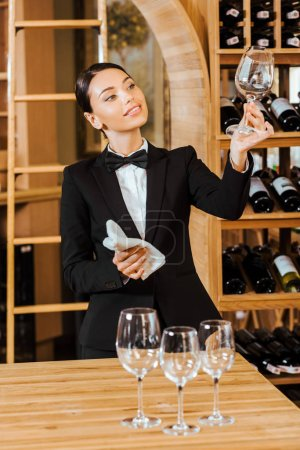 attractive female wine steward checking clear glass at wine store