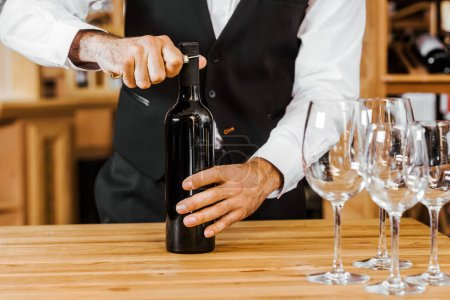 cropped shot of sommelier opening bottle of wine at store