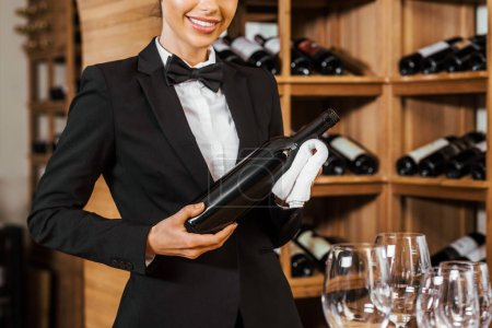 cropped shot of smiling female wine steward holding bottle at wine store