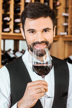 handsome smiling sommelier sniffing red wine from glass at wine store