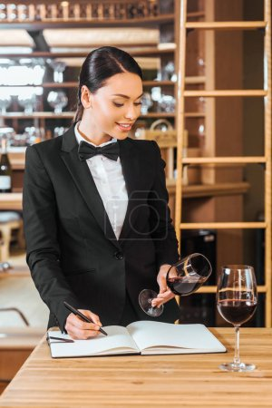 beautiful female wine steward looking at glass of wine and writing in notebook at wine store