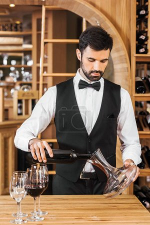 handsome young wine steward pouring wine into decanter at wine store