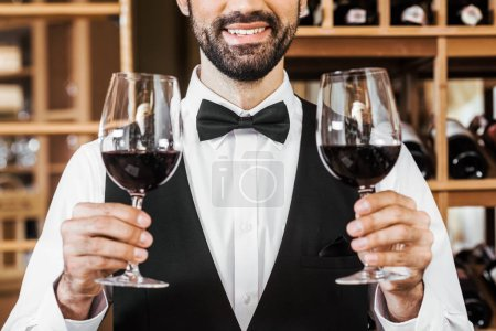 cropped shot of smiling young sommelier holding two glasses of red wine at wine store