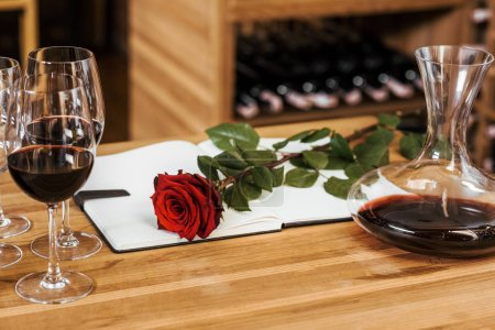 close-up shot of decanter of red wine with notebook and red rose on wooden table at wine storage