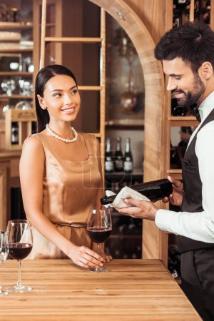 wine steward pouring wine for young attractive woman at wine store