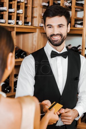 wine steward taking golden credit card from female customer at wine store