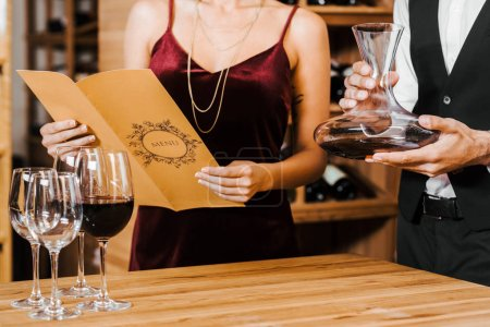 cropped shot of wine steward holding decanter while client reading menu list at wine store