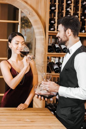 wine steward holding decanter of wine in front of female client at wine store
