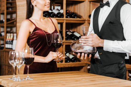 cropped shot of wine steward holding decanter of wine in front of female client at wine store